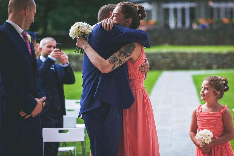 Bridesmaid hugs groom