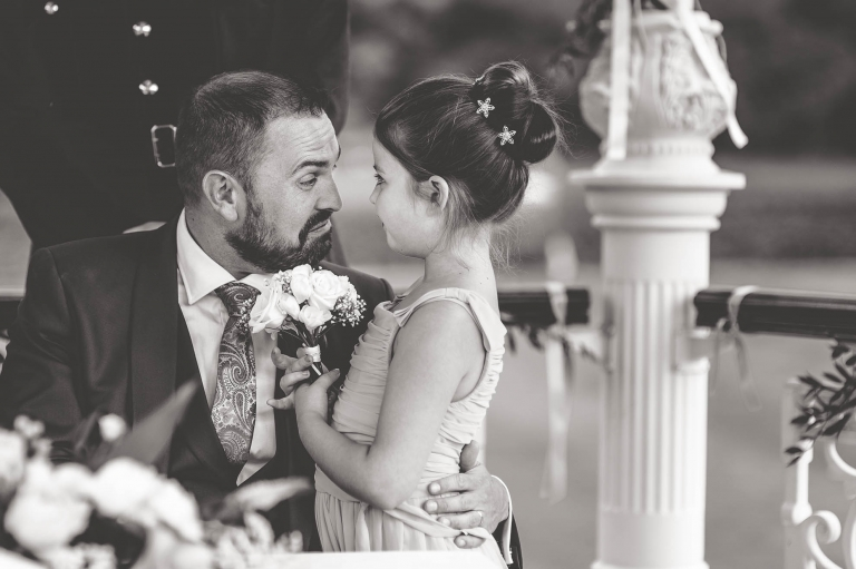 Flower girl and groom smile at each other