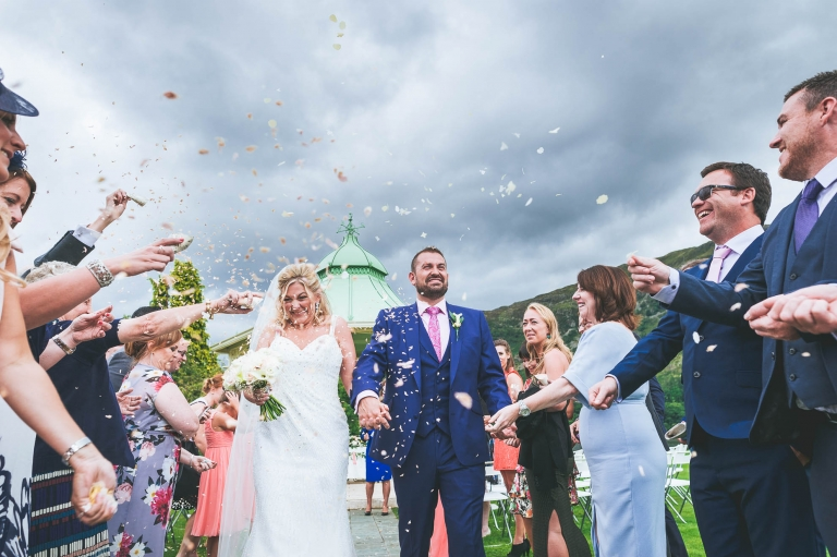Guests throw confetti over the newlyweds