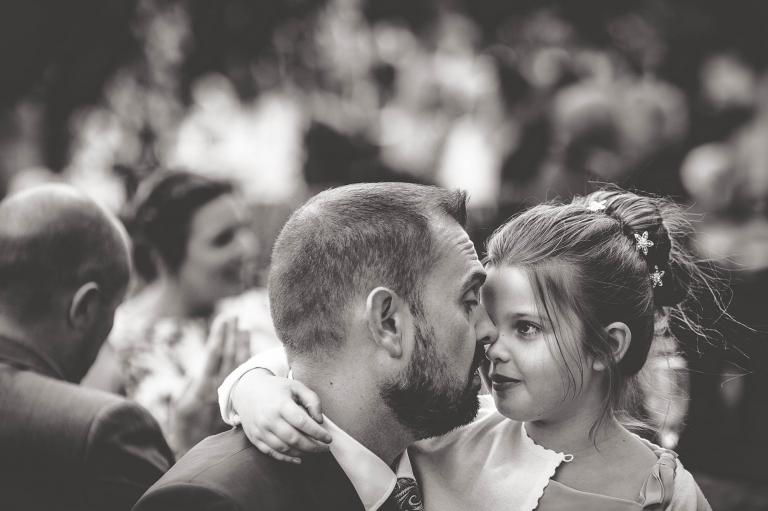 Little girl hugs groom