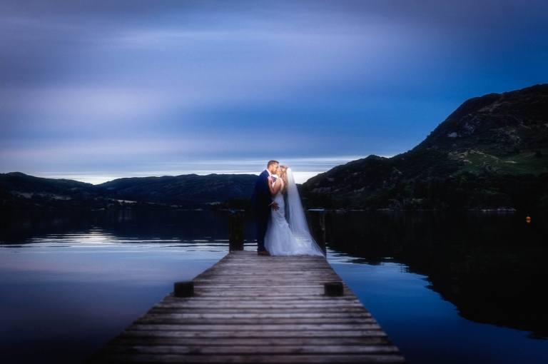 Bride and groom stand at end of jetty kissing