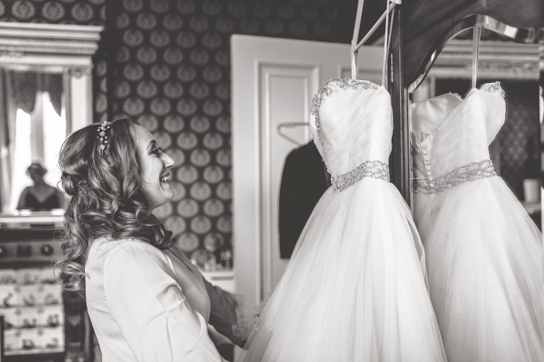 Bride looking at dress and smiling