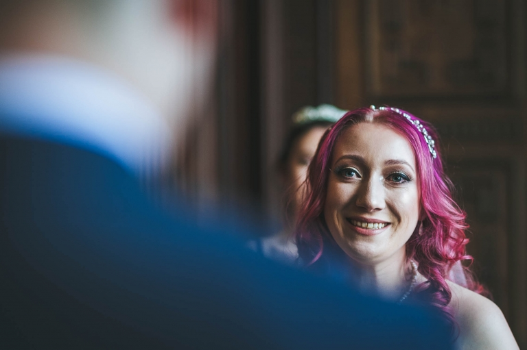 bride smiles at groom during vows