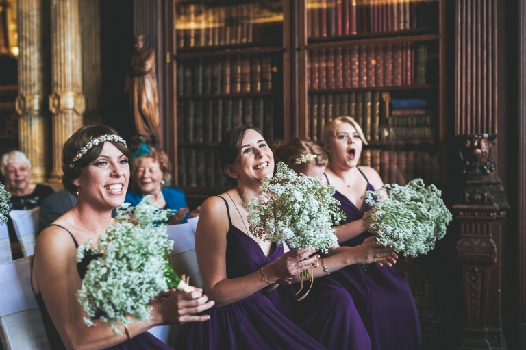 Bridesmaids smile at bride and groom