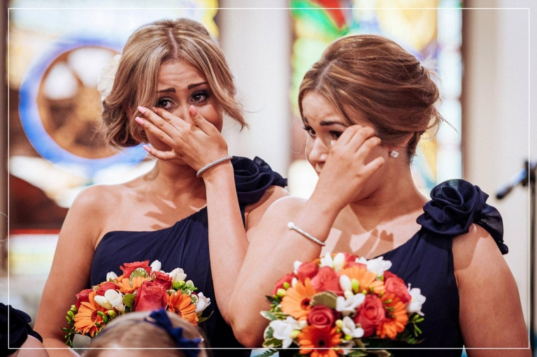 bridesmaids crying as bride walks up the aisle in church