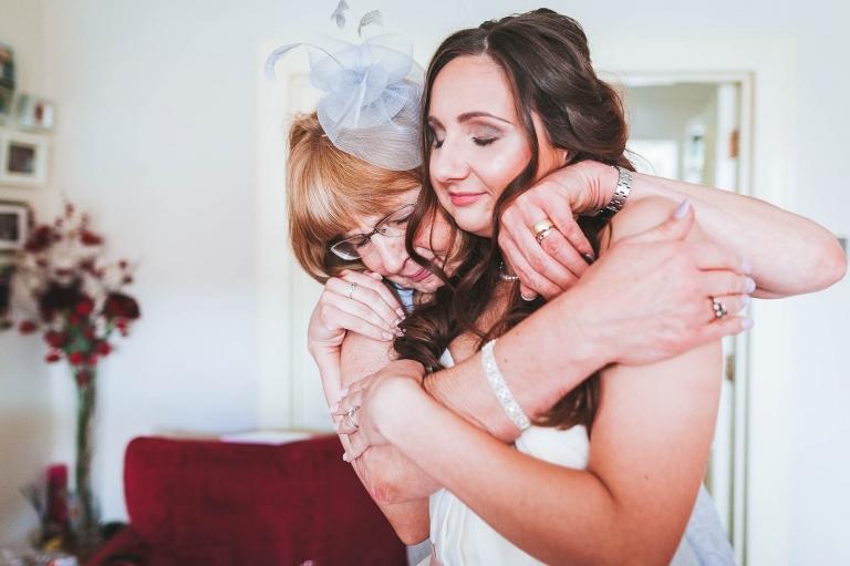 mum gives bride a hug