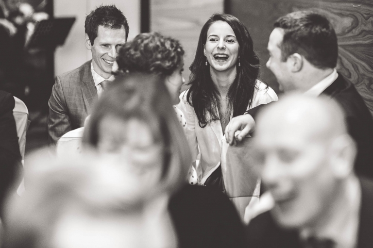 wedding guests sharing a joke before ceremony
