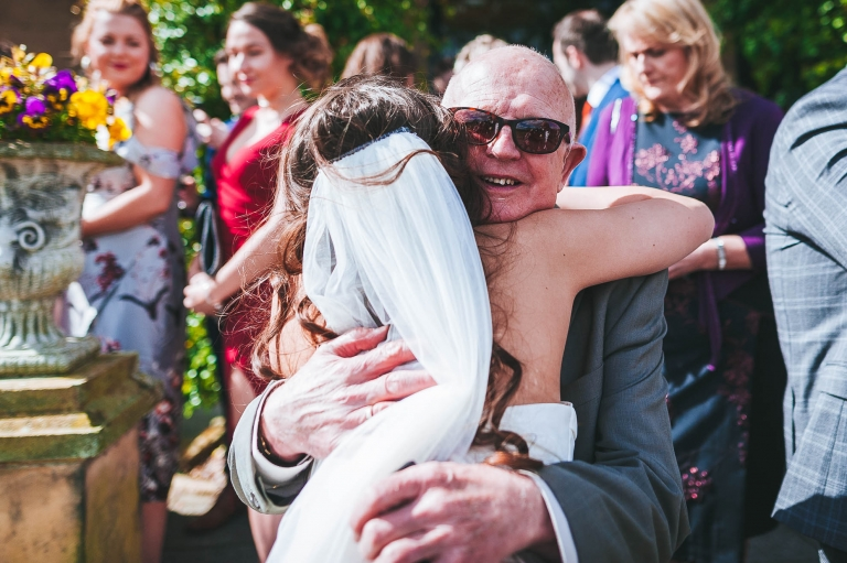 Guest hugs the bride at the drinks reception