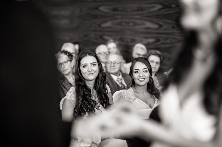 Bridesmaids smile as they watch the exchange of vows