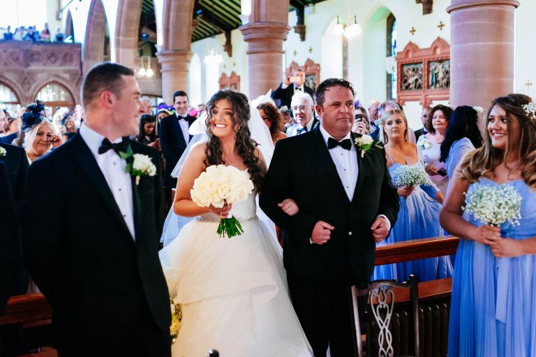 bride greets groom as she arrives at the altar
