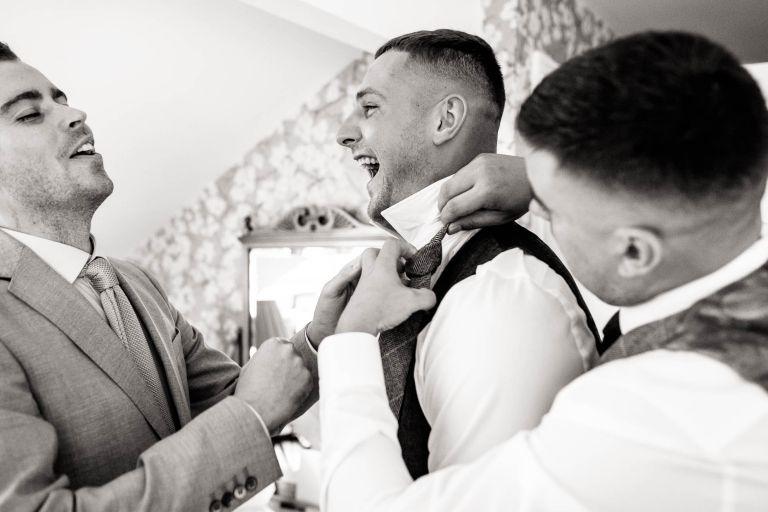 Groom shares a joke with groomsmen