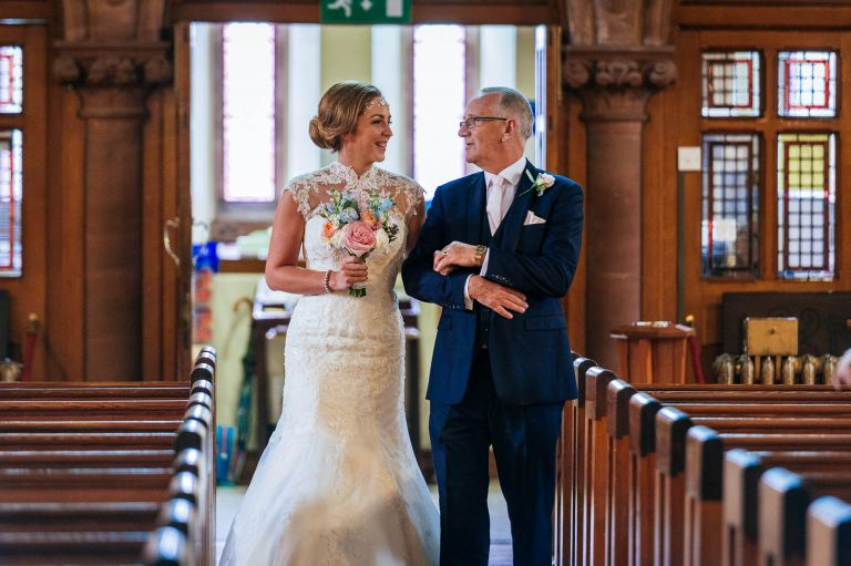 bride and her dad look at each other before they walk down the aisle.