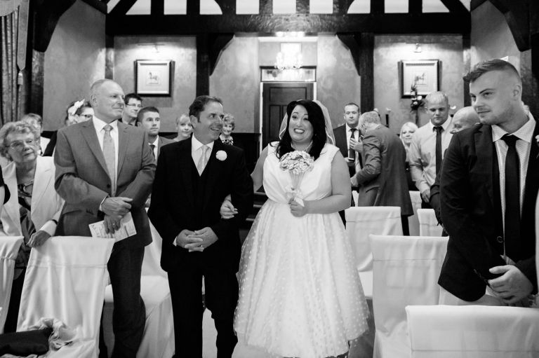 Bride gives groom a big smile as she walks up the aisle