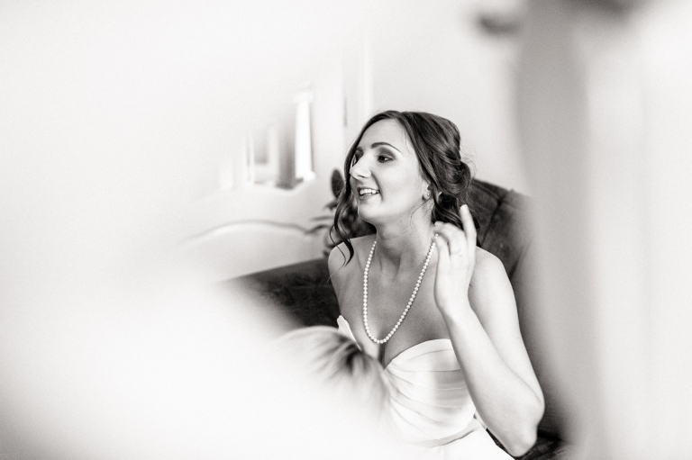 bride smiles as she puts her wedding dress on