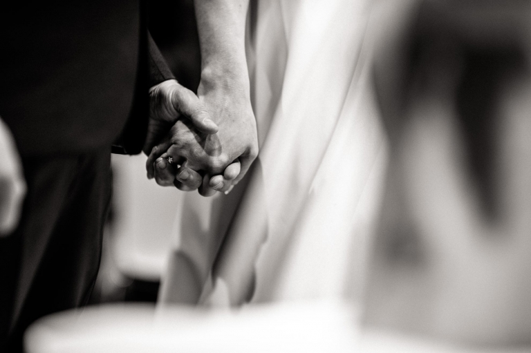 bride and groom holds hands during wedding ceremony