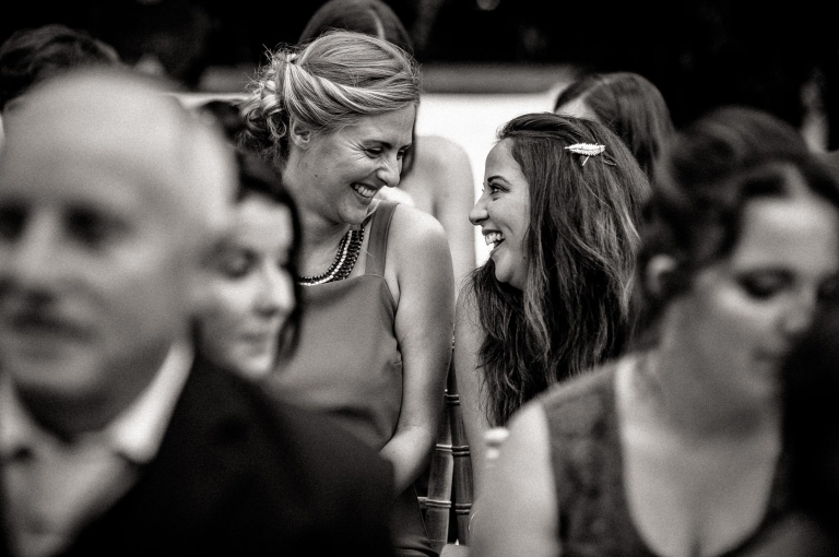 wedding guests laugh together during the ceremony