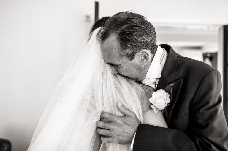 dad hugs the bride as he sees her in her dress for the first time