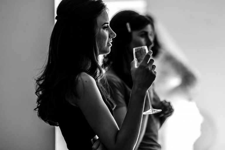 Bridesmaid enjoys a glass of champagne