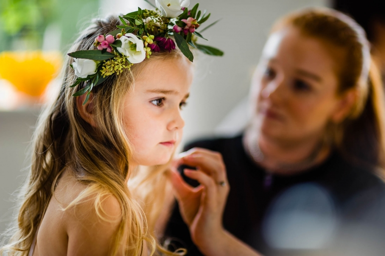 A flower girl has her flower garland fitted