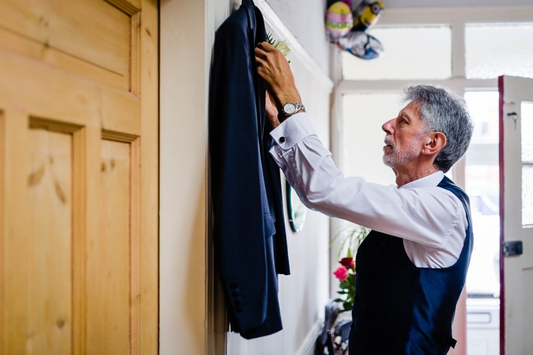 father of the bride puts his suit jacket on