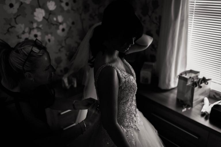 the bridesmaid adjusts the brides wedding dress