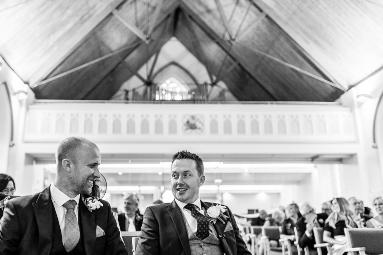 The groom and best man share a joke while waiting at the church