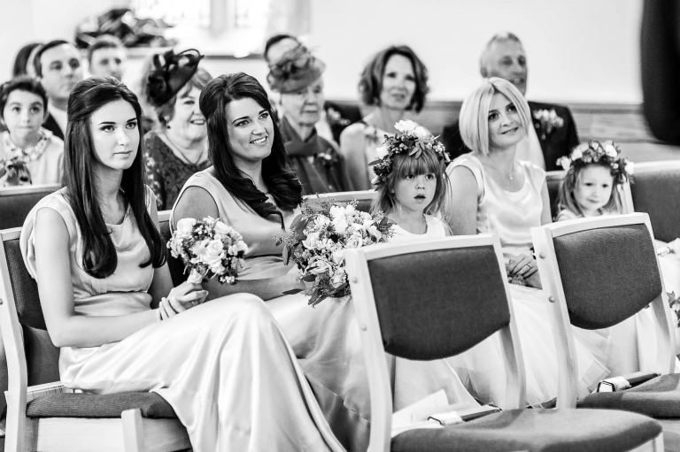 the bridesmaids and flower girls look on during the exchange of vows