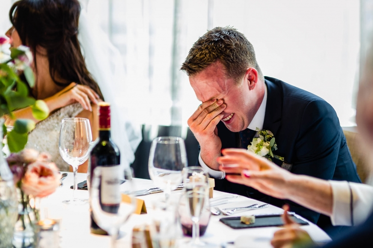 groom's embarrassed laugh as the best man makes fun of him