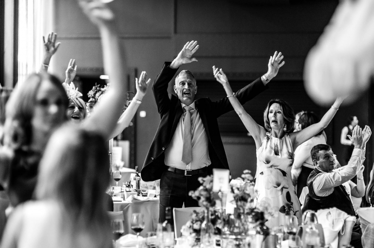 guests wave their hand in the air as the singing waiters perform