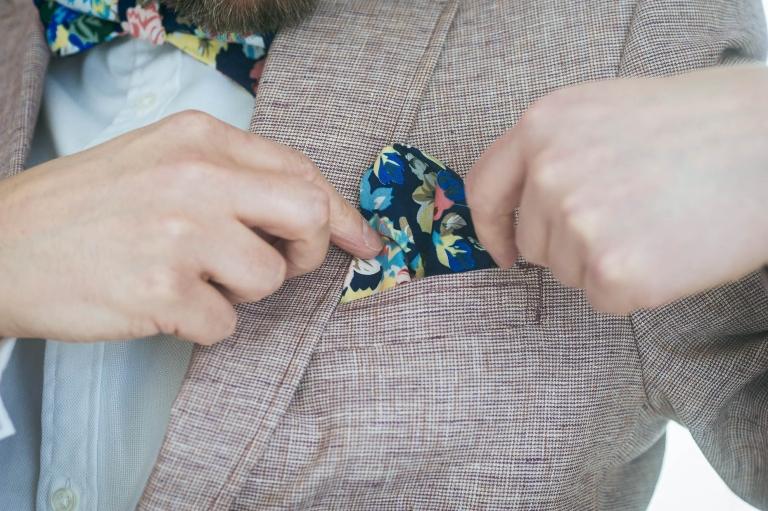 Luke fixes his kerchief on his wedding suit