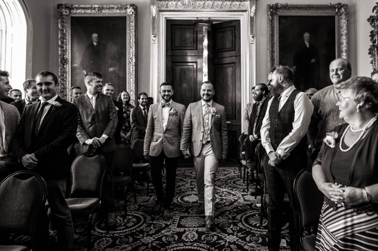 Luke and mike walk down the aisle of the wedding ceremony room in Liverpool Town Hall.