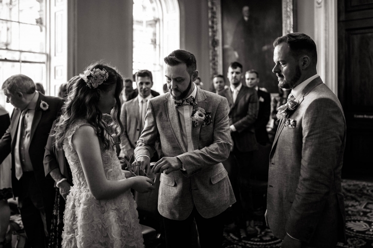 flower girl passes the rings to Luke