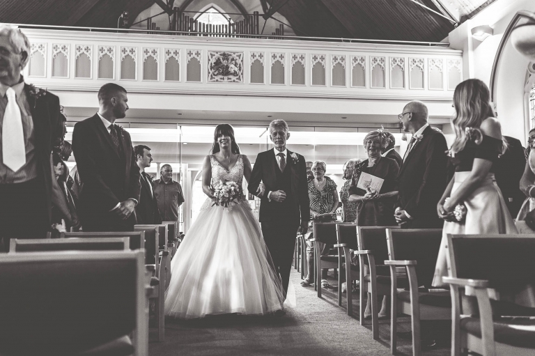 the bride walks up the church aisle with her father