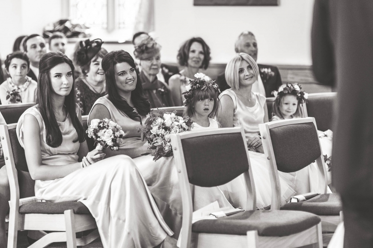 the bridesmaids and flower girls look on during the vows