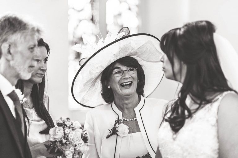 The mother of the bride laughs as during the signing of the register
