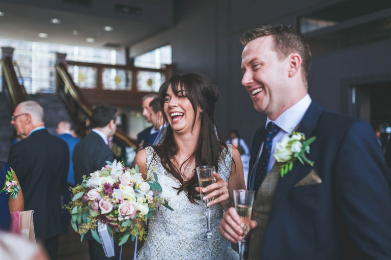 bride and groom share a joke with guests