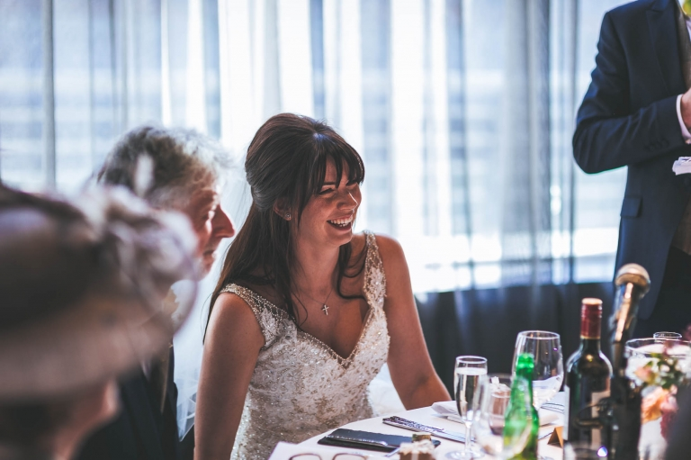 bride laughs during grooms speech