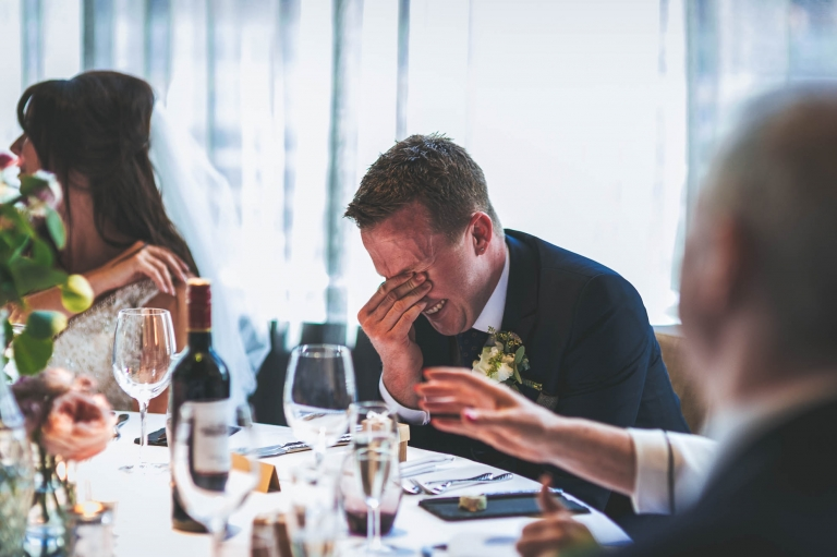 groom laughs embarrassingly as the best man makes fun of him