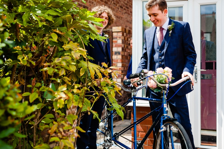Groom and his best man with tandem cycle