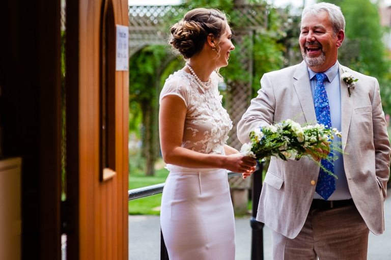 Bride shares a joke with the father of the bride outside the church