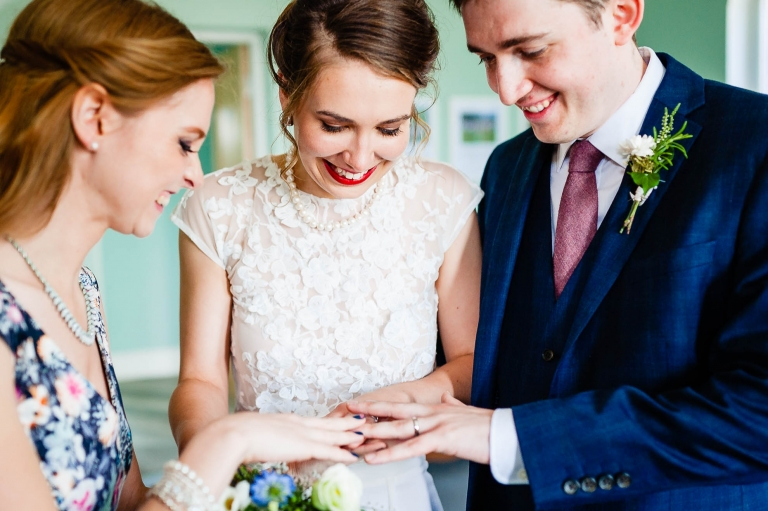 Bride and groom show wedding rings to witness