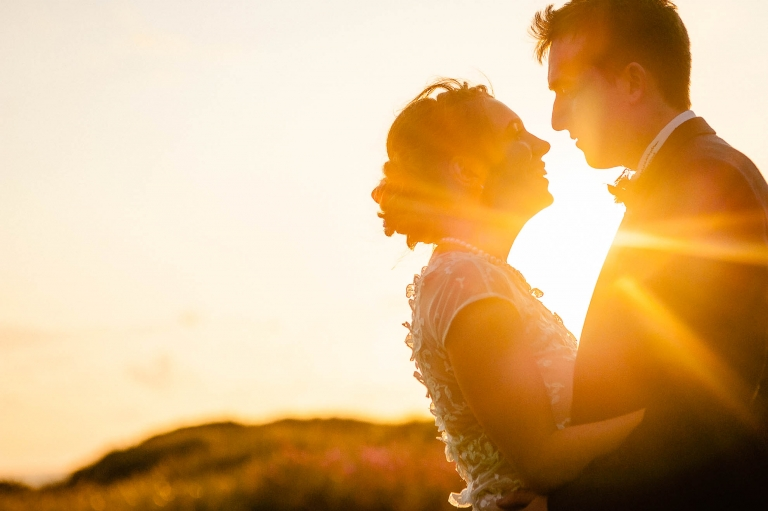 Close up of bride and groom in sunset