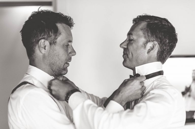 Same sex couple adjusting each others neckties