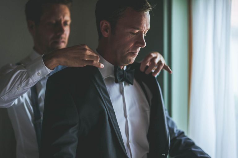 Partner helping groom into his suit