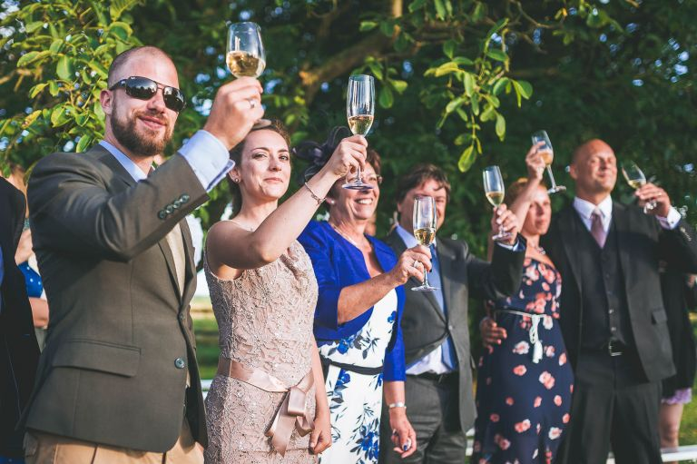 Wedding guests lift their glasses up to toast