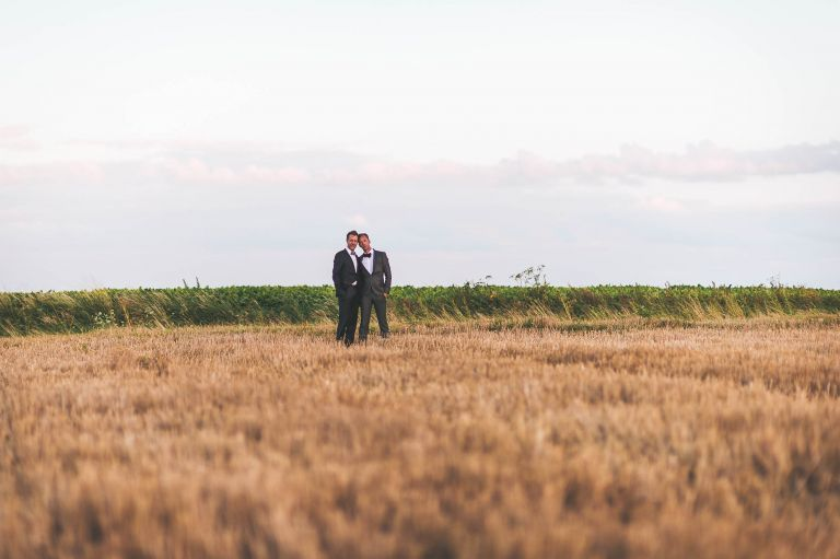 The newlyweds hold each other in a field