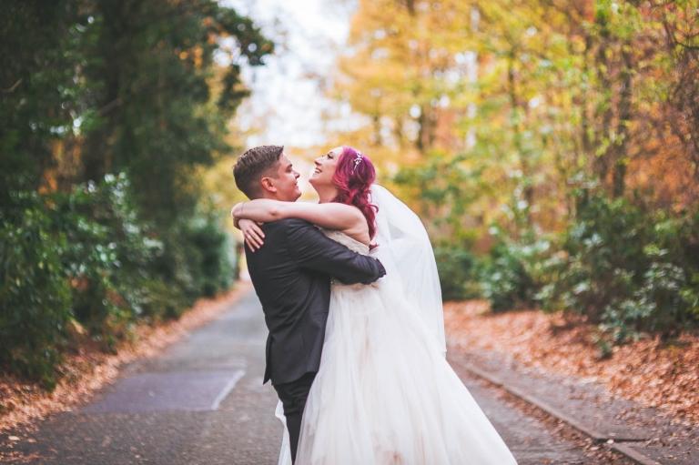 Bride picks bride up laughing