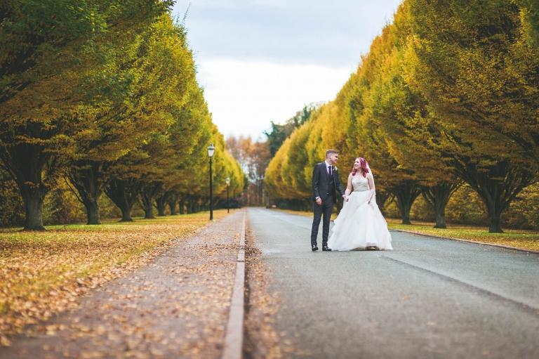 Bride and groom walk along road