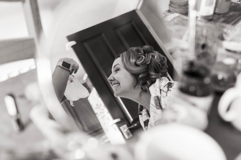 Bridesmaid reflection in mirror as she gets ready for the big day