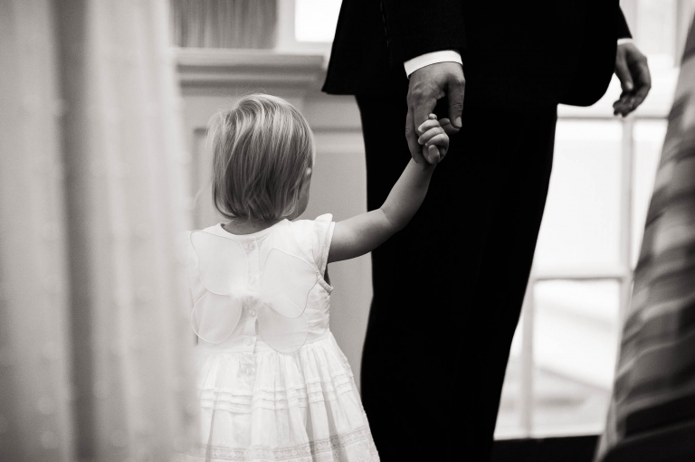 Little flower girl with her father the groom